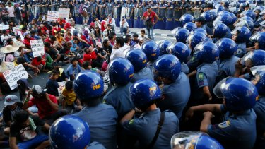 Security is tight in Manila as police confine a group of protesters along a street after attempting to march towards the venue for this week's APEC summit.