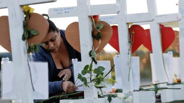 Cece Navarrette places flowers at a cross for her cousin, Bailey Schweitzer, who was among those killed during the mass shooting in Las Vegas.