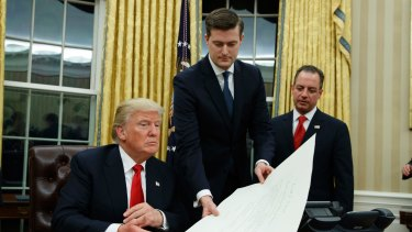 White House Chief of Staff Reince Priebus, right, watches as White House Staff Secretary Rob Porter, center, hands President Donald Trump a confirmation order for James Mattis as Defense Secretary.