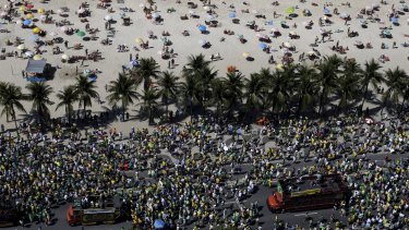 Sun-lovers in Copacabana are outnumbered by protesters on Sunday.