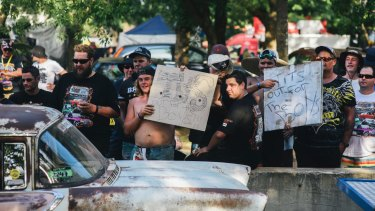 Men hold up signs along Tuff Street during Summernats.