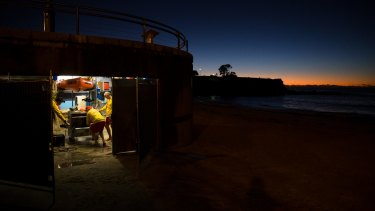 Members of the Coogee Surf Life Saving Club clear out their boatshed which was inundated with water and sand during the storms.