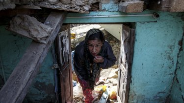 An earthquake survivor visits her collapsed house in Sankhu, on the outskirts of Kathmandu, on Tuesday.