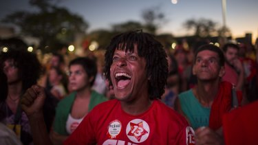 A pro-government demonstrator reacts as they watch an MP cast a vote not to impeach President Dilma Rousseff, on April 17.