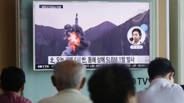 People watch a TV news program showing a file footage of North Korea's ballistic missile that the North claimed to have launched from underwater, at Seoul Railway station.