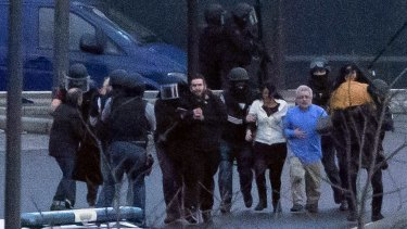 Security officers escort released hostages after they stormed a kosher grocery store.