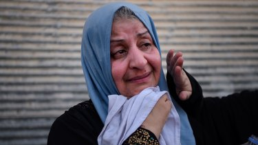 A woman weeps with relief as she waits to be taken to a displaced people's camp at a screening point in western Mosul.
