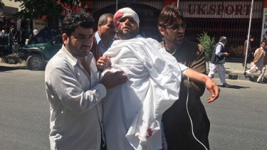 People carry an injured man after a bomb exploded in Kabul's diplomatic district, in Afghanistan on Wednesday.