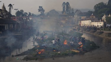 Flames rise from burning funeral pyres during the cremation of victims of Saturday's earthquake, at the Pashupatinath temple on the banks of Bagmati river, in Kathmandu.
