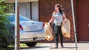 A police officer carries evidence from a house in Werribee on Tuesday.