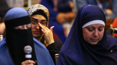 A woman cries as another woman gives a testimony during the conference.
