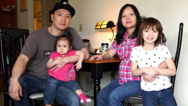Adam Crapser, left, with daughters Christal, one, Christina, five, and his wife, Anh Nguyen, in the family's living room in Vancouver, Washington state.