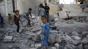 Children walk over the rubble of a house destroyed by an air strike by the Saudi-led coalition on the Yemeni capital, Sanaa.