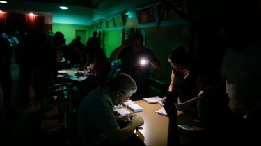 Officials use mobile phone lights to count votes during a power outage at a school assigned to be a polling station by the Catalan government in Barcelona, Spain.