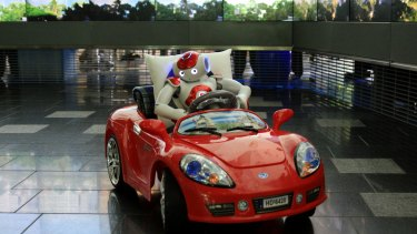 One of the NAO robots drives a small car at Queensland University of Technology.