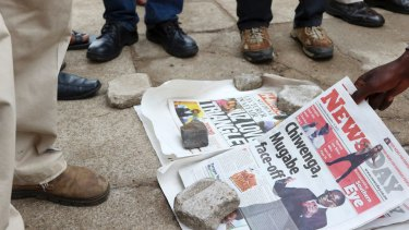 Zimbabweans check newspapers as armed soldiers patrol the streets in Harare.