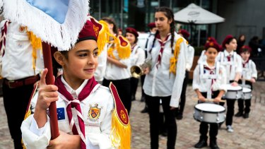 Proud new Aussie: Flag bearer Farah, 9, leads the Australian Syrian Youth Marching Band around Federation Square.