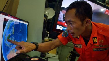 Last contact: An official from Indonesia's national search and rescue agency in Medan, North Sumatra, points to the position where AirAsia flight QZ 8501 went missing off the waters of Indonesia.
