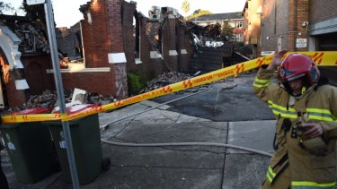 A firefighter inspects the ruins of the Macedonian Orthodox Church of the Resurrection in Frederick Street, Rockdale.