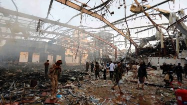 People inspect the aftermath of an air strike in the Yemeni capital, Sanaa, which killed at least 100 people and injured hundreds more.