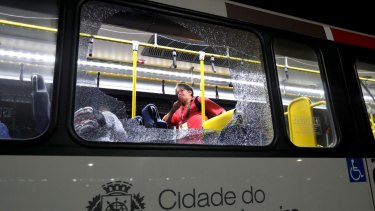 A member of the media stands near a shattered window on a bus in the Deodoro area of Rio de Janeiro after it came under attack.