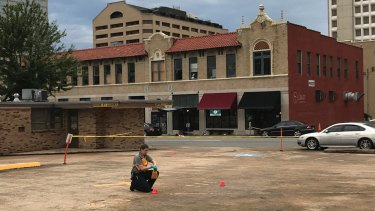 An investigator collects evidence near an Arkansas nightclub where 25 people were shot.
