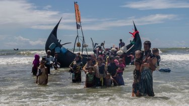 A Rohingya Muslim man walks to shore carrying two children in Bangladesh after they arrived on a boat from Myanmar.