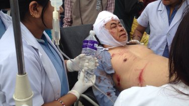An Injured person receives treatment outside the Medicare Hospital in Kathmandu, Nepal.
