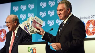 Treasurer Joe Hockey holds up a report with OECD secretary-general Angel Gurria in Cairns.