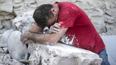 A man leans on rubble following an earthquake in Amatrice, Italy.