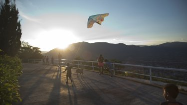 A child flies a kite as others look out over the city of Iguala, Mexico. Iguala was thrust into the limelight in 2014 when three students were killed and 43 others disappeared allegedly at hands of the local police.