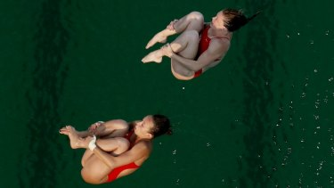 """It's so green"": United States' Amy Cozad, top, and Jessica Parratto before diving into the green pool."