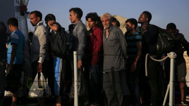 Migrants line up onboard an Italian coast guard vessel before disembarking at the port of Kos on Friday.
