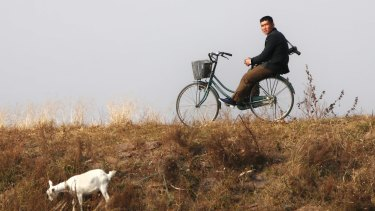 With a gun on his shoulder, a young North Korean man on a bicycle watches a Chinese tourist boat passing by in Sinuiju on the North Korean side of the Chinese border.