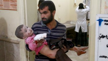 A Syrian man carries his son to a field hospital after the Syrian and Russian armies carried out air strikes in Aleppo.