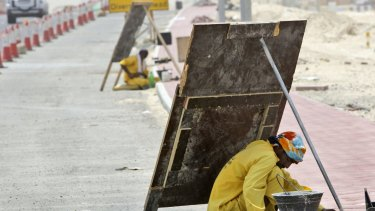 An Asian labourer avoids the direct sun by using the shade of a wooden sign as he works on a manhole beside a road under construction in Dubai, United Arab Emirates.
