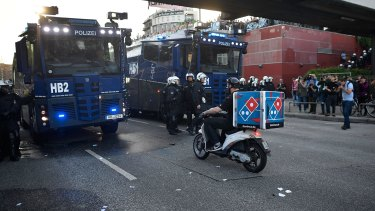 """HAMBURG, GERMANY - JULY 06: A pizza delivery man rides a scooter towards police vehicles during the """"Welcome to Hell"""" protest march on July 6, 2017 in Hamburg, Germany. Leaders of the G20 group of nations are arriving in Hamburg today for the July 7-8 economic summit and authorities are bracing for large-scale and disruptive protest efforts tonight at the """"Welcome to Hell"""" anti-G20 protest. (Photo by Alexander Koerner/Getty Images)"""