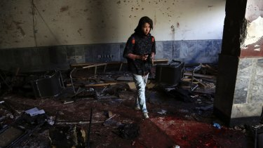 An Afghan photographer walks through the scene of a suicide attack on a Shiite cultural center in Kabul, Afghanistan on Thursday.