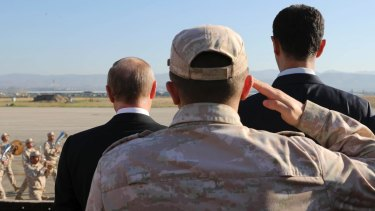 Russian President Vladimir Putin, left, and Syrian President Bashar al-Assad, right, watch troops marching at the Hemeimeem air base in Syria, on Monday.