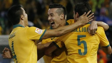 You beauty: Australia's Jason Davidson celebrates with teammates Tim Cahill and Mark Milligan after scoring a goal against UAE during their Asian Cup semi-final at Hunter Stadium.