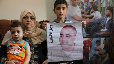 Amal el-Halabi holds her grandson Fares, 18 months old, while her grandson Amro, 7, holds a picture of his father Mohammed el-Halabi, World Vision's Gaza operations manager, who Israel accuses of diverting funds to Hamas. The alleged figures exceed the total World Vision budget for Gaza.
