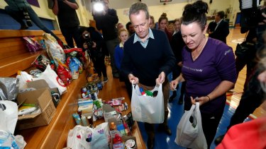 Opposition Leader Bill Shorten donates cleaning products to a fundraiser organised by the local basketball team in Latrobe on Thursday.