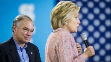 Senator Tim Kaine listens while Hillary Clinton speaks at a campaign event in Annandale, Virginia, on July 14.