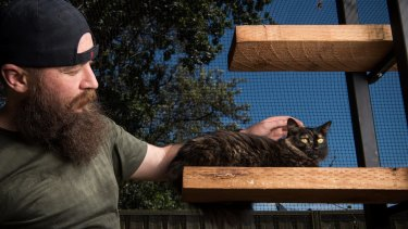 Matt Black of Parramatta, pictured here with Isis, keeps his cats in a purpose built cat enclosure in his backyard.