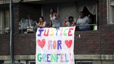 People watch from a balcony as people walk during a demonstration following the fire at Grenfell Towers.