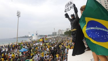 "An anti-government demonstrator dressed as Batman holds a placard reading ""Out Dilma"" during a protest against Brazil's President Dilma Rousseff on Copacabana beach in Rio de Janeiro earlier this month."