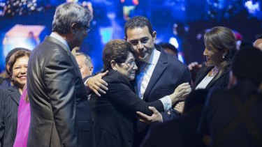 Jimmy Morales, of the National Front of Convergence party, centre, with his mother Celita Cabrera as they celebrate winning the presidential run-off election on Monday.