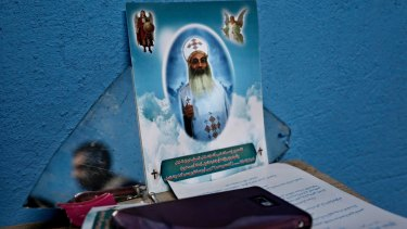A Christian man, reflected in a mirror, sits near a photo of priest who was killed by IS militants.