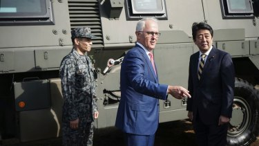 Australian Prime Minister Malcolm Turnbull, centre and Japanese counterpart Shinzo Abe at Narashino Exercise Area east of Tokyo on Thursday.