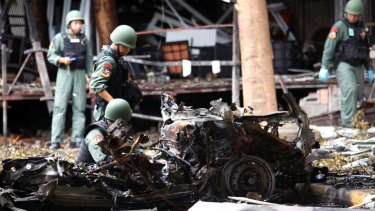 Thai bomb squad officers examine the wreckage of a car after an explosion outside a hotel in Pattani province, southern Thailand, on Wednesday.